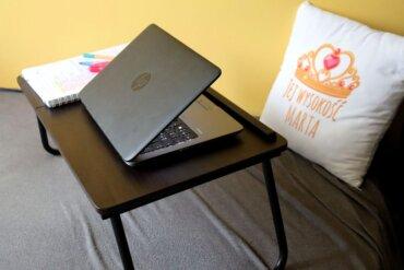 laptop na stoliku, na łóżku, poduszka